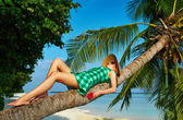 Woman lying down on a palm tree at tropical beach — Stock Photo