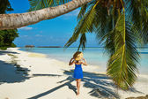 Woman in blue dress on a beach at Maldives — Stock Photo