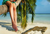 Woman sitting on a palm tree at tropical beach — Stock Photo