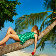 Stock Photo: Woman lying down on a palm tree at tropical beach