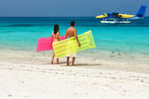 Couple with inflatable rafts looking at seaplane on beach — Stock Photo