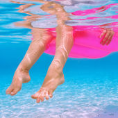 Woman relaxing on inflatable mattress, view from underwater — Stock Photo