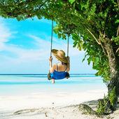 Frau im blauen kleid schwingt am strand — Stockfoto