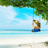 Woman in blue dress swinging at beach — Stock Photo