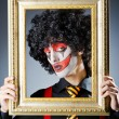 Clown with picture frames in studio - Foto Stock