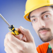 Man with a screwdriver in studio - Stock Photo