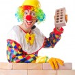 Bad construction concept with clown laying bricks — Stock Photo #12648865