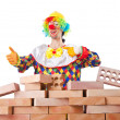 Bad construction concept with clown laying bricks — Stock Photo #12846231
