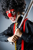Funny clown with bat in studio — Stock Photo