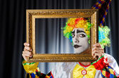 Clown with picture frames in studio — Stock Photo
