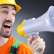 Construction worker with loudspeaker in studio - Stock Photo