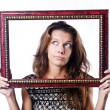 Young woman with picture frame on white — Stockfoto