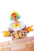 Bad construction concept with clown laying bricks — Stock Photo