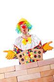 Slechte bouwconcept met clown houdende van bakstenen — Stockfoto