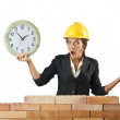 Female builder and clock on white — Stockfoto