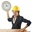 Female builder and clock on white - Foto Stock