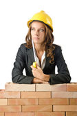 Young female builder near brick wall — Stock Photo