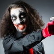 Evil clown with gun in dark room — Stock Photo #13872829
