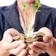 Businesswoman with seedlings and coins — Stock Photo #13872902