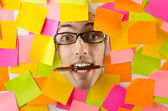 Man's face through paper and reminders — Stock Photo