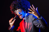 Young singer in afro wig singing at disco — Stok fotoğraf