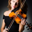 Woman with violin in dark room — Stock Photo
