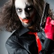 Evil clown with gun in dark room — Stock Photo #14049622