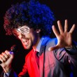 Young singer in afro wig singing at disco — Stock Photo #14049645