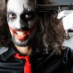 Evil clown with gun in dark room — Stock Photo #14049651