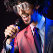 Young singer in afro wig singing at disco — Stock Photo #14049663