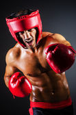 Boxer with red gloves in dark room — Stock Photo