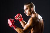 Boxeador con guantes rojos en cuarto oscuro — Foto de Stock