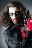 Onda clown med pistol i mörkt rum — Stockfoto