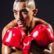 Boxer with red gloves in dark room — Stock Photo #14368735