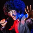 Young singer in afro wig singing at disco — Stock Photo