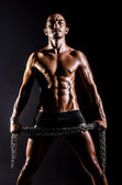 Bodybuilder with chains in dark — Stock Photo