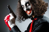 Evil clown with gun in dark room — Stock Photo