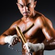 Strong man with nunchaku — Stock Photo
