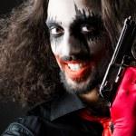 Evil clown with gun in dark room — Stock Photo #14763285