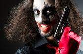 Evil clown with gun in dark room — Stock Photo