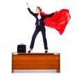 Superwoman standing on the desk — Stock Photo