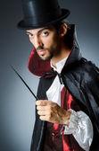 Magician doing tricks in dark room — Stock Photo