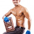 Stock Photo: Muscular builder with bricks on white