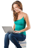 Student with netbook sitting on books — Stock Photo