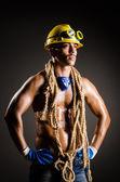 Construction worker in dark studio — Stock Photo