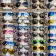 Many sunglasses on display in shop — Zdjęcie stockowe