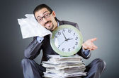 Man with clock and pile of papers — Stock Photo