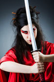 Female sword warriod in dark studio — Stock Photo