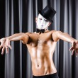 Muscular actor with mask against curtain — Stock fotografie