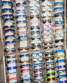 Many sunglasses on display in shop — Stock Photo